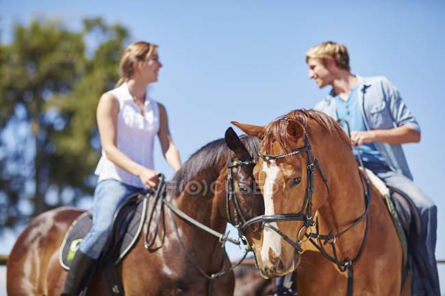 Молодая пара верхом на лошадях — стоковое фото