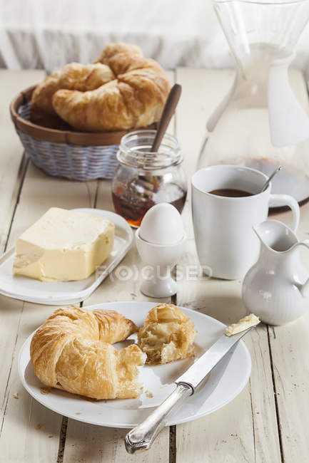 Breakfast with croissant, egg, coffee, honey and butter — Stock Photo