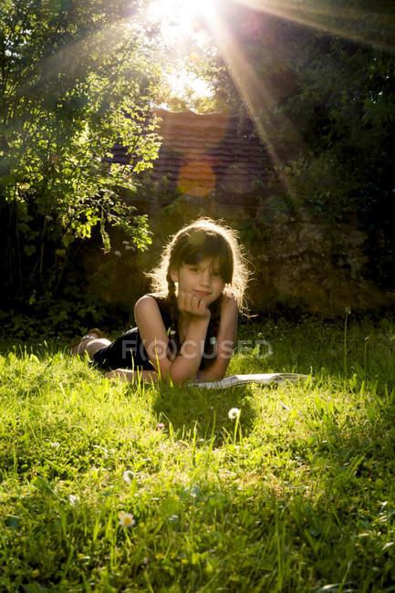 Портрет девушки, лежащей на лугу с книгой — стоковое фото