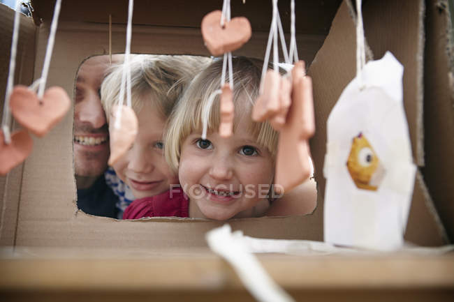 Father and kids playing with selfmade toys — Stock Photo