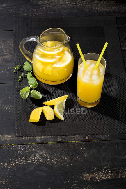 Cooled soft drink with mango, lemon and mint on black wooden table — Stock Photo