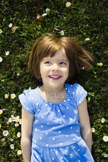 Портрет усміхнений дівчинка, лежачи на луг — стокове фото