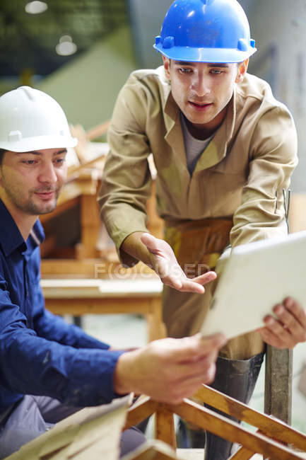 Construction worker and foreman discussing roof beams — Stock Photo