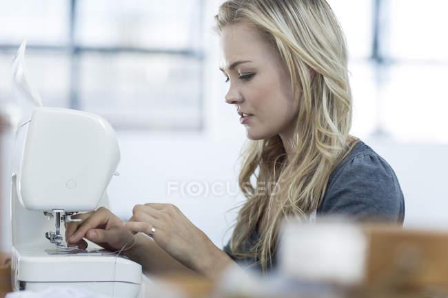 Молода жінка введення Нитки швейні машини — стокове фото