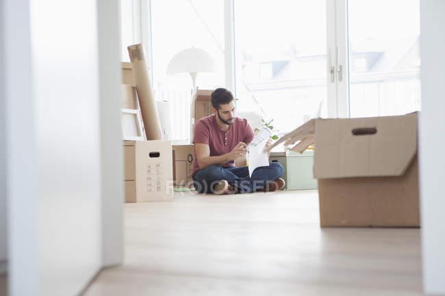 Jeune homme dans nouvel appartement avec des boîtes en carton, tenant le plan au sol — Photo de stock