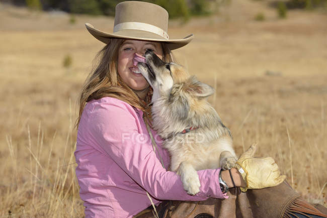 Cowgirl with her dog — Stock Photo
