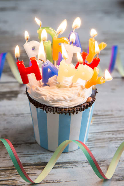 Birthday muffin with chocolate buttons and lighted candles — Stock Photo