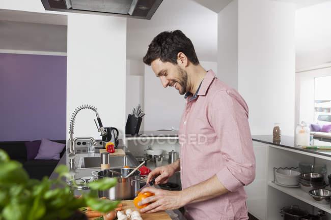 Sorridente homem cozinhando na cozinha — Fotografia de Stock