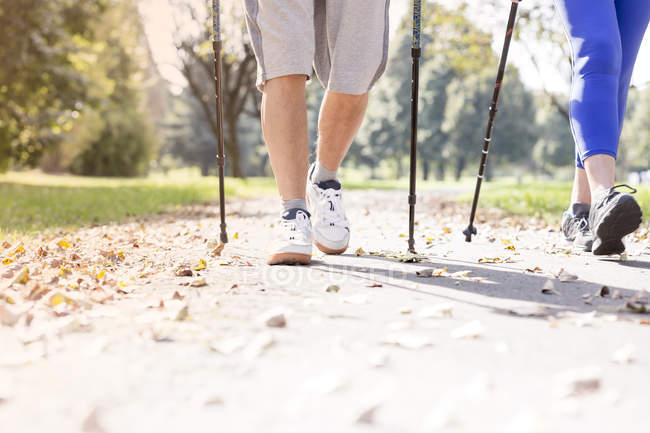 Legs of senior couple doing Nordic Walking together in a park — Stock Photo