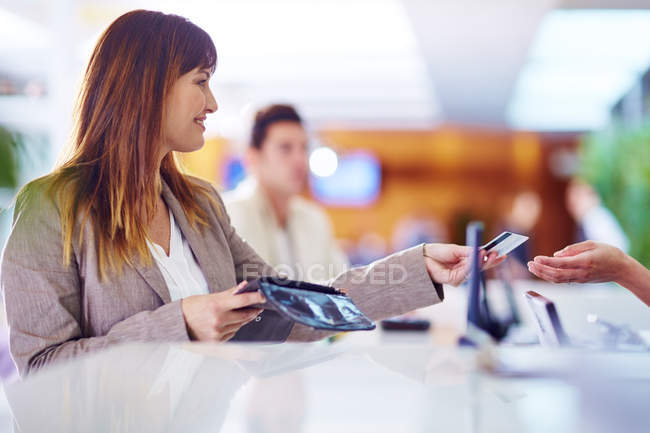 Businesswoman paying with credit card at hotel recption — Stock Photo