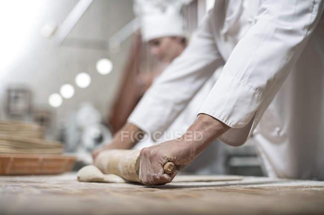 Bäcker rollt Teig aus — Stockfoto