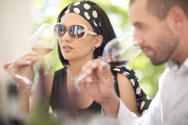 Homem e mulher examinando vinho tinto em uma sessão de degustação de vinhos — Fotografia de Stock