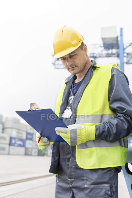 Man with clipboard wearing safety vest at container port — Stock Photo