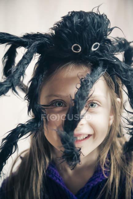 Fillette souriante avec spider jouet sur sa tête — Photo de stock