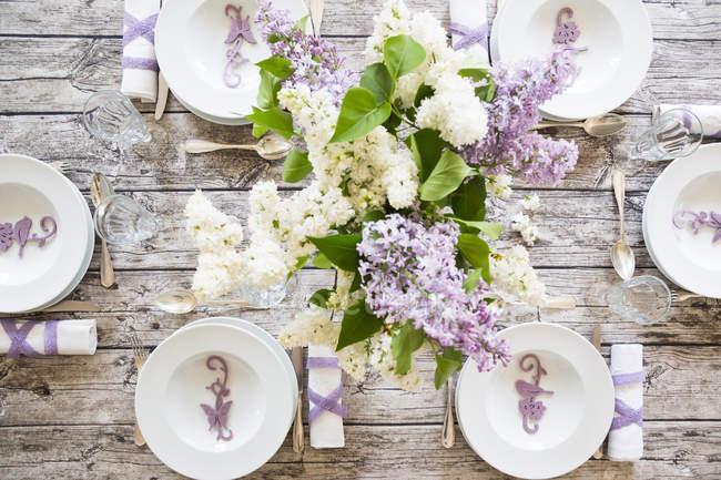 Table couchée décorée de lilas blanc et violet — Photo de stock