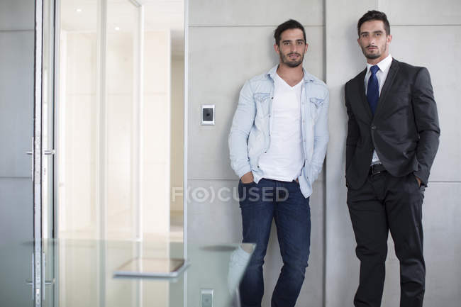 Casually and formally dressed twin males in office — Stock Photo