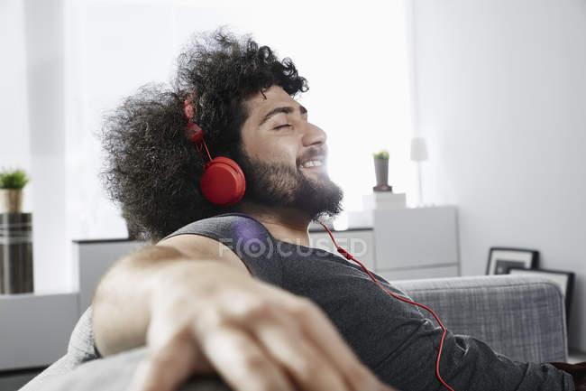 Junger Mann sitzt zu Hause auf Couch und hört Musik mit Kopfhörern — Stockfoto