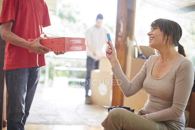 Mujer que recoge un pedido de pizza en casa - foto de stock
