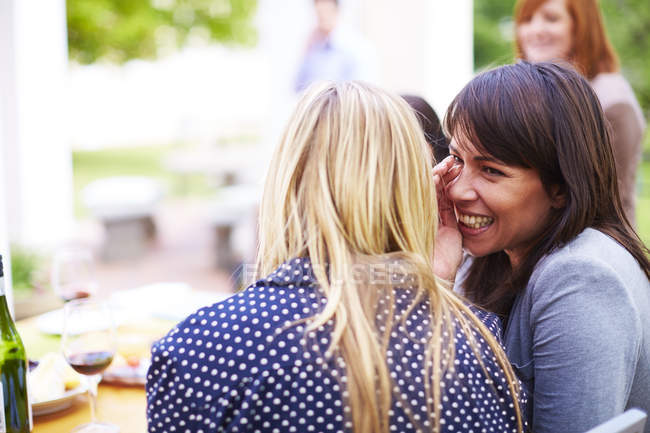 Happy woman whispering to friend — Stock Photo