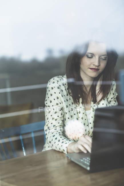 Junge Frau hinter Fensterscheibe mit Laptop — Stockfoto