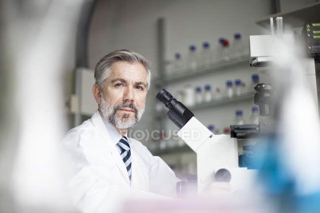 Portrait of scientist in laboratory with microscope — Stock Photo