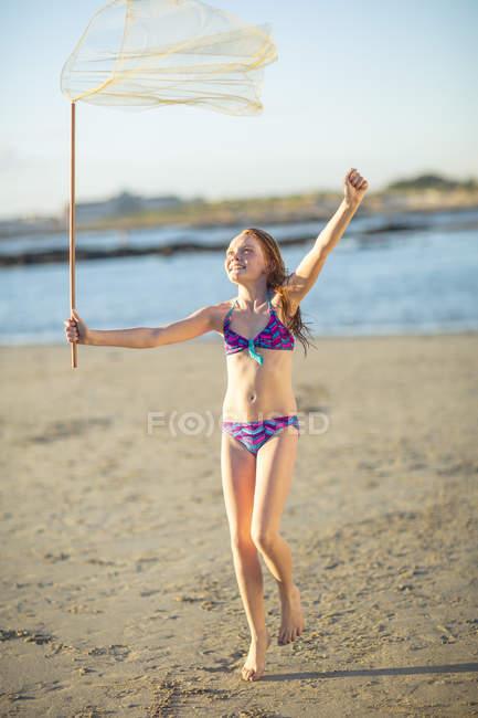 Fille heureuse sur la plage en cours d'exécution avec un filet papillon — Photo de stock
