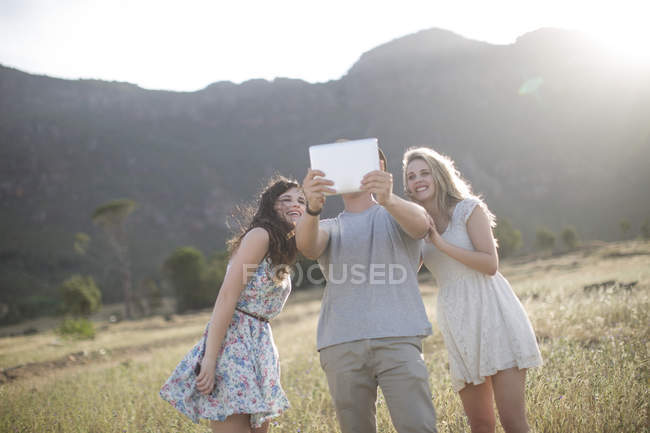 South Africa, Friends taking selfie pictures with tablet in field — Stock Photo