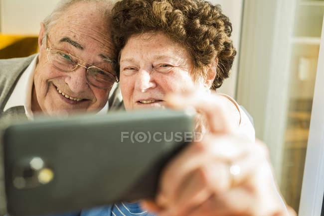 Couple aîné prenant un selfie avec smartphone à la maison — Photo de stock