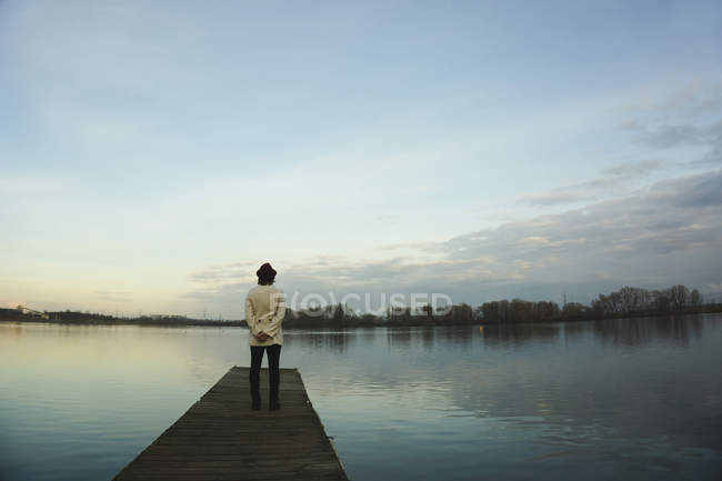Germany, Roxheim, woman standing on wooden boardwalk at water — Stock Photo