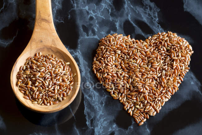 Red rice shaped like a heart and wooden spoon of red rice — Stock Photo