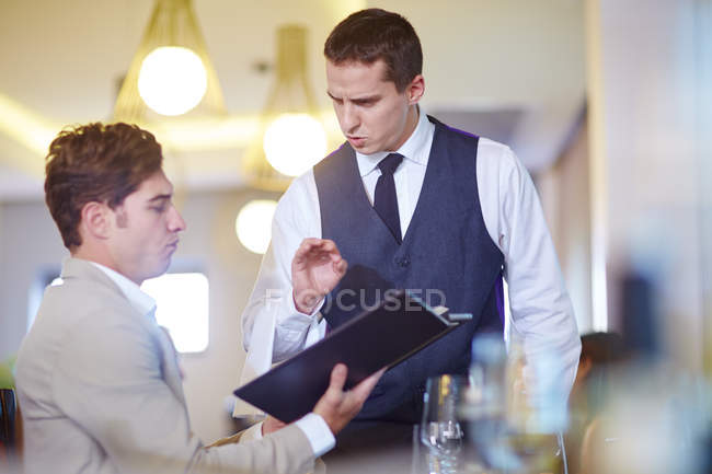 Businessman placing an order with waiter at hotel restaurant — Stock Photo
