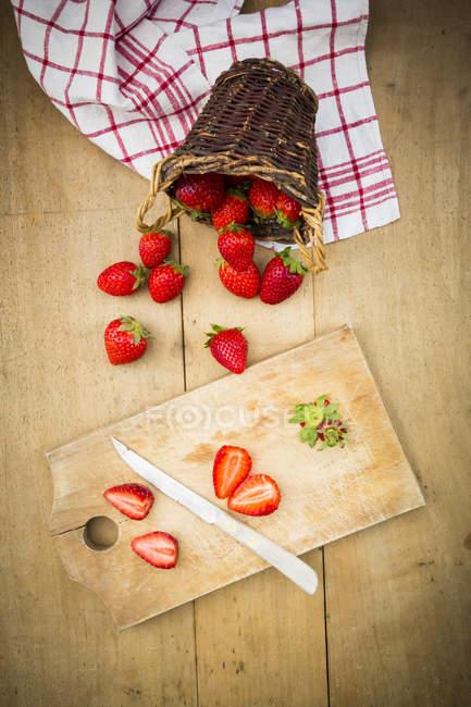 Morangos fatiados e todo com cortar placa — Fotografia de Stock