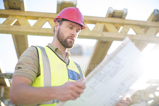 Construction worker reading plan at construction site — Stock Photo