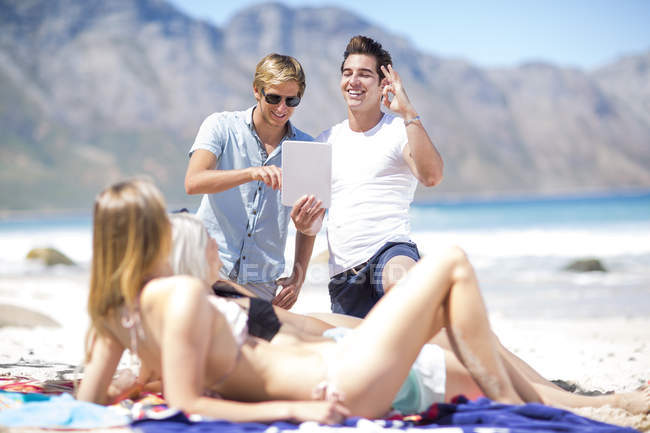 Молоді люди, що знімати фотографії з планшета молодих жінок, сонячні ванни — стокове фото