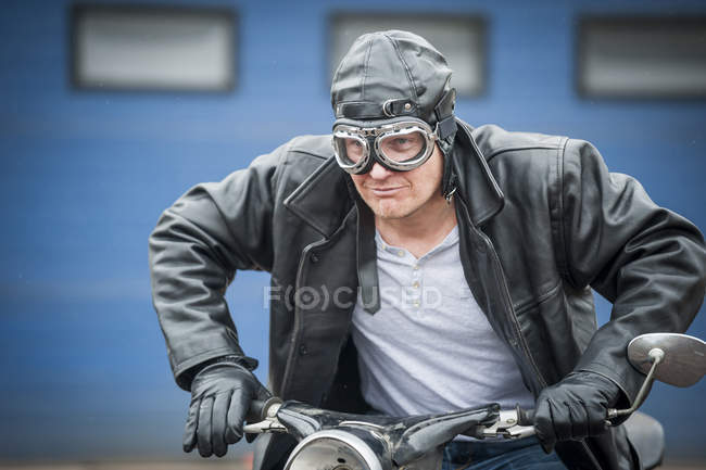 Man in leather jacket and googles sitting on vintage moped — Stock Photo