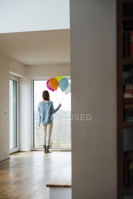 Junge Frau mit Luftballons, die aus dem Fenster schauen — Stockfoto