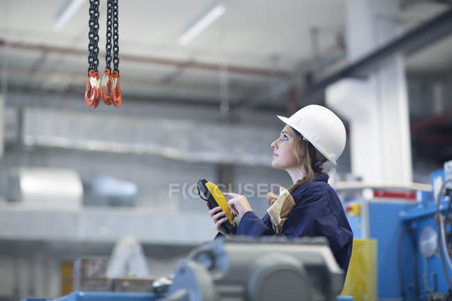Technician in factory hall using regulator for hook — Stock Photo