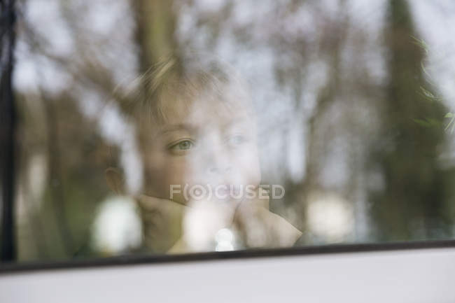 Ritratto di ragazzo serio che osserva dalla finestra accanto al riquadro di vetro — Foto stock