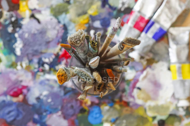 Glass with paintbrushes on artist palette — Stock Photo