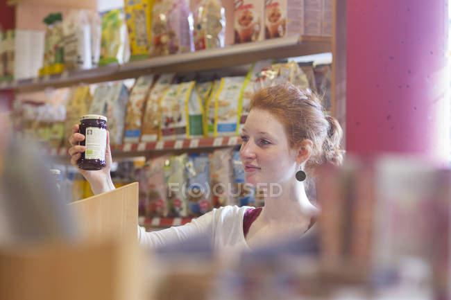 Помощница продавщицы сортирует товары в магазине цельнозерновой продукции — стоковое фото