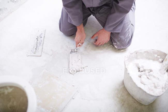 Строитель с помощью мозаики на полу — стоковое фото