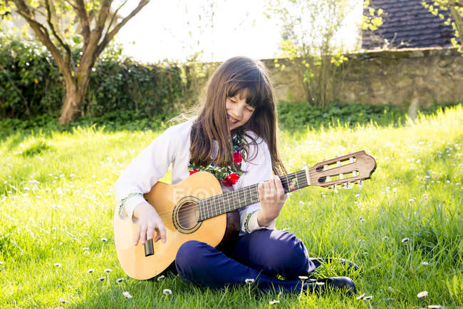 Laughing girl sitting on a meadow playing guitar — Stock Photo