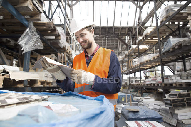 Warehouseman in storehouse looking at building material — Stock Photo