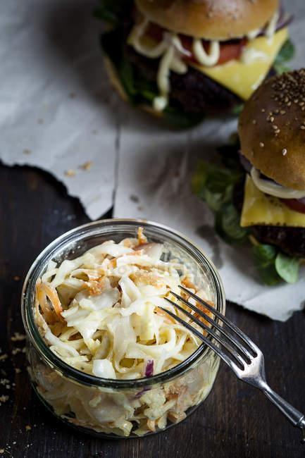 Домашний чизбургер и капустный салат в стеклянном горшке с вилкой — стоковое фото