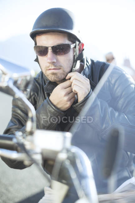 Man on motorcycle tying helmet strap — Stock Photo