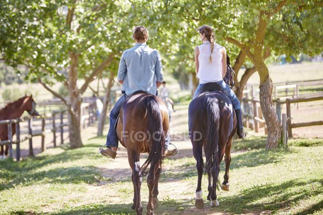 Молодая пара едет в загоне — стоковое фото