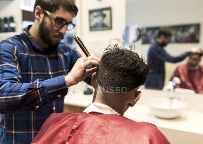 Парикмахер бреет волосы молодого человека в парикмахерской — стоковое фото