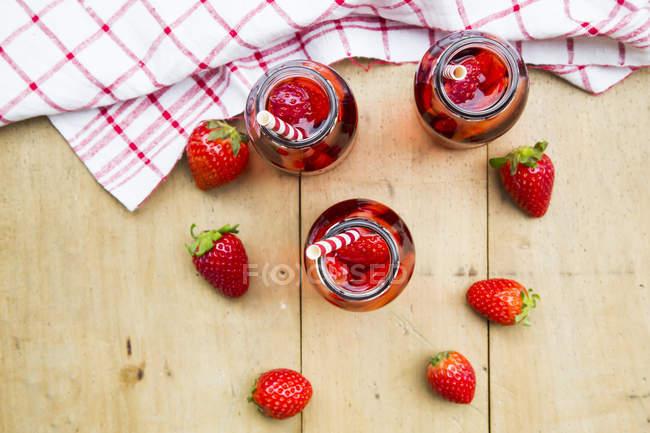 Vue de dessus de trois bouteilles en verre de limonade aux fraises maison et fraises fraîches — Photo de stock