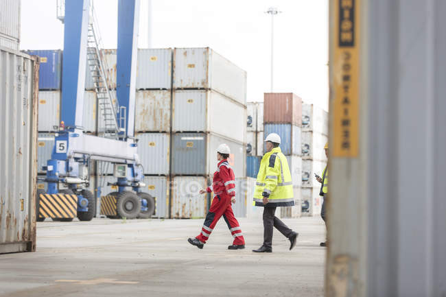 Woman and two men wearing protective clothing walking at container port — Stock Photo