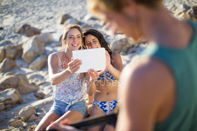 Ragazze che scattano una foto con un tablet di uomo che suona la chitarra acustica — Foto stock